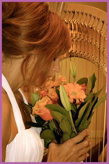 Bride holding bouquet in front of wedding harp